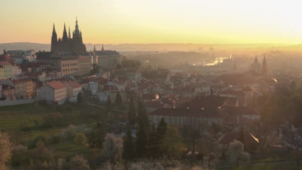 Der malerische Blick auf die Ziegeldächer Prags bei Sonnenaufgang im Frühling. Die Türme der St.-Veits-Kirche und der St.-Nikolaus-Kirche vom Aussichtspunkt Petrin aus gesehen. Romantisches goldenes Sonnenlicht am Morgen und blühende Bäume im Park
