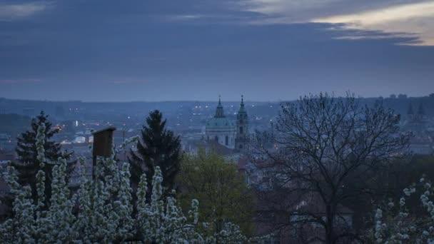 Scénický pohled na panorama Prahy při východu slunce na jaře. Věže kostela sv. Mikuláše z Petřínského vrchu. Romantické slunce svítí ráno a kvetou stromy s ptačí budkou v městském parku. Noční přechod z jednoho dne na druhý, záznam časových prodlev 4k