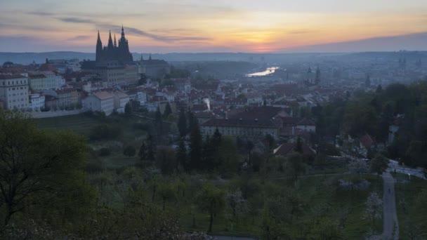 Scénický pohled na panorama Prahy při východu slunce na jaře. Věže katedrály sv. Víta na Pražském hradě a kostel sv. Mikuláše z pohledu Petřína, kvetoucí stromy v městském parku. Záběry časových prodlev 4k