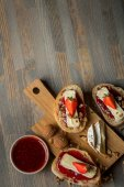 bowl with fruit jam and delicious sandwiches with strawberries, nuts and cheese on wooden board, top view with copy space