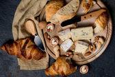 Fotografia Degustazione di formaggi assortiti brie e blu con croissant su sfondo scuro. Concetto di cibo francese