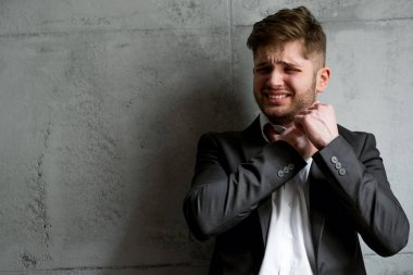 Young businessman in suit with emotion and depression on face touching his neck