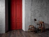 Vintage-Holzstühle im Zimmer mit grauer Betonwand und roter Tür