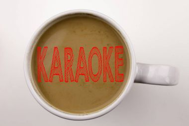 Word, writing Karaoke text in coffee in cup. Business concept for Singing Karaoke Music on white background with copy space. Black text with red word.