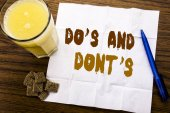Handwriting Announcement text showing Do s And Do Not Donts. Business concept for Guide Allowed written on tissue paper on the wooden background with pen and healthy juice in the restaurant