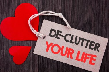 Handwriting Announcement text showing De-Clutter Your Life. Business concept for Free Less Chaos Fresh Clean Routine written on Price tag with Red words on the wooden background.