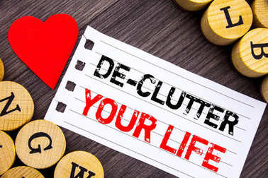 Handwriting text showing De-Clutter Your Life. Conceptual photo Free Less Chaos Fresh Clean Routine written on tear note paper sticky note on the wooden background with heart.