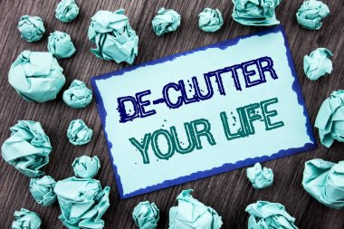 Conceptual hand writing text showing De-Clutter Your Life. Concept meaning Free Less Chaos Fresh Clean Routine written on Sticky note paper folded paper on the wooden background.