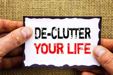 Writing text showing  De-Clutter Your Life. Concept meaning Free Less Chaos Fresh Clean Routine written on Sticky Note Paper Holding Hand with Finger.