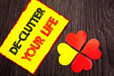Text showing De-Clutter Your Life. Business photo showcasing Free Less Chaos Fresh Clean Routine written on Sticky Note Paper with Love Heart Next to it on the wooden background.