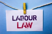 Fotografie Text sign showing Labour Law. Conceptual photo Employment Rules Worker Rights Obligations Legislation Union written on White Note Paper hanging with rope on the plain background Clip.