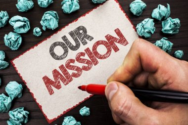 Text sign showing Our Mission. Conceptual photo Goal Motivation Target Growth Planning Innovation Vision written by Man Holding Marker on Cardboard Piece on the wooden background.