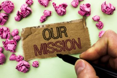 Writing note showing  Our Mission. Business photo showcasing Goal Motivation Target Growth Planning Innovation Vision written by Man Holding Marker on Tear Cardboard Piece plain background.