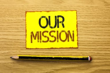 Conceptual hand writing showing Our Mission. Business photo showcasing Goal Motivation Target Growth Planning Innovation Vision written on Yellow Sticky Note on wooden background Pencil.