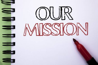 Handwriting text Our Mission. Concept meaning Goal Motivation Target Growth Planning Innovation Vision written on Notebook Book on the plain background Marker next to it.