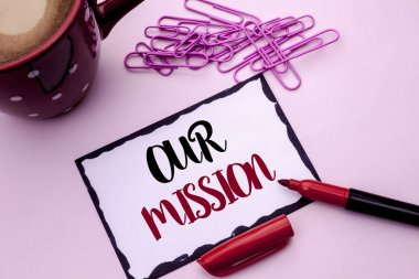 Text sign showing Our Mission. Conceptual photo Goal Motivation Target Growth Planning Innovation Vision written on Sticky Note Paper on the plain background Marker Cup Pins next to it.