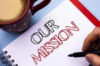 Writing note showing  Our Mission. Business photo showcasing Goal Motivation Target Growth Planning Innovation Vision written on Notebook Book Holding Pen on the plain background Coffee Cup.