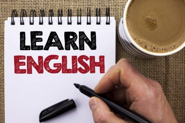 Text sign showing Learn English. Conceptual photo Study another Language Learn Something Foreign Communication written by Man Holding Marker on Notebook Book on the jute background Coffee Cup.