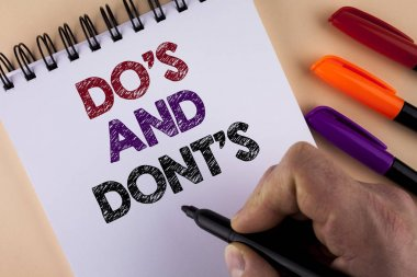 Word writing text Do'S And Don'Ts. Business concept for What can be done and what cannot be knowing right wrong written by Man with Marker on Notepad on the plain background Markers next to it