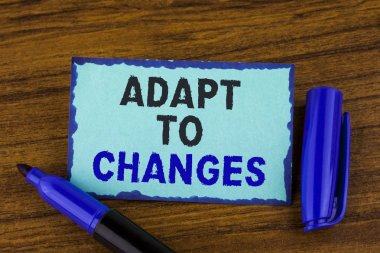 Text sign showing Adapt To Changes. Conceptual photo Innovative changes adaption with technological evolution written on Sticky Note paper on the wooden background Marker next to it.