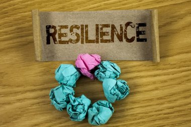 Writing note showing  Resilience. Business photo showcasing Capacity to recover quickly from difficulties Persistence written on Folded Cardboard Paper Piece wooden background Paper Balls