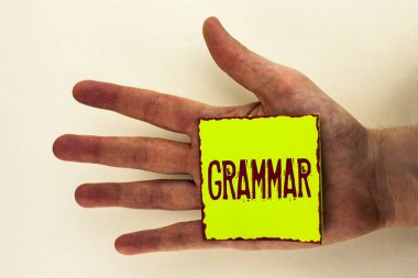 Word writing text Grammar. Business concept for System and Structure of a Language Correct Proper Writing Rules written on Sticky Note Paper placed on the Hand on the plain background.