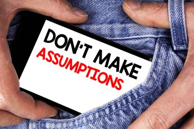 Handwriting text writing Do not Make Assumptions. Concept meaning predict events future without clue Alternative Facts written on Mobile phone screen holding by man on the jeans background.