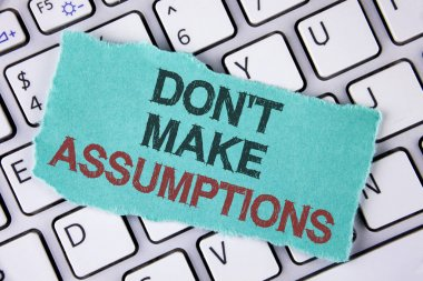 Handwriting text writing Do not Make Assumptions. Concept meaning predict events future without clue Alternative Facts written on tear Sticky Note Paper placed on the Laptop.
