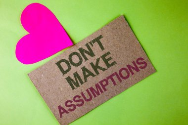 Conceptual hand writing showing Do not Make Assumptions. Business photo text predict events future without clue Alternative Facts written on Cardboard Piece on the plain background Heart next to it
