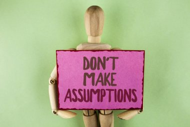 Handwriting text writing Do not Make Assumptions. Concept meaning predict events future without clue Alternative Facts written on Sticky note paper holding by Wooden Robot Toy on plain background.