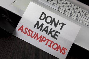 Writing note showing  Do not Make Assumptions. Business photo showcasing predict events future without clue Alternative Facts written on White Sticky Note Paper placed on wooden Table Laptop Mouse