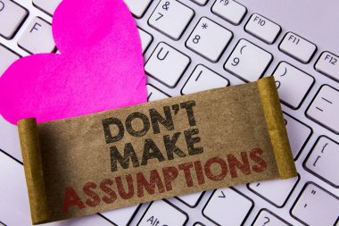 Writing note showing  Do not Make Assumptions. Business photo showcasing predict events future without clue Alternative Facts written on Folded Cardboard Paper Piece placed on White Keyboard Heart.