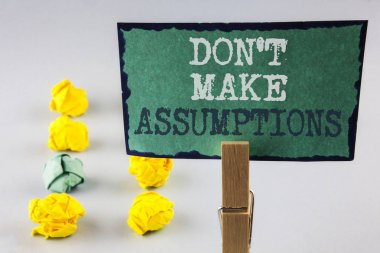 Handwriting text writing Do not Make Assumptions. Concept meaning predict events future without clue Alternative Facts written on Sticky Note Paper holding by Clip plain background Paper Balls