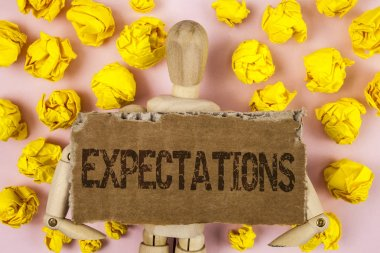 Conceptual hand writing showing Expectations. Business photo showcasing Huge sales in equity market assumptions by an expert analyst written on Tear Cardboard piece on pink background wooden Toy