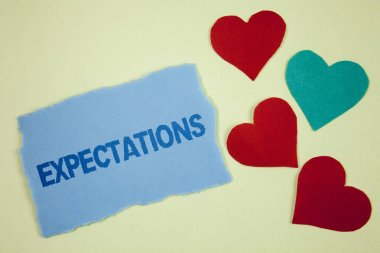Handwriting text Expectations. Concept meaning Huge sales in equity market assumptions by an expert analyst written on Tear sticky note paper piece on plain background paper Hearts next to it.