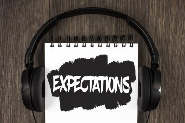Word writing text Expectations. Business concept for Huge sales in equity market assumptions by an expert analyst written on Notepad on the wooden background Headphone next to it.