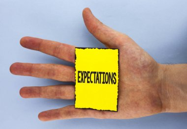 Conceptual hand writing showing Expectations. Business photo showcasing Huge sales in equity market assumptions by an expert analyst written on Yellow Sticky Note Paper on plain background Hand.