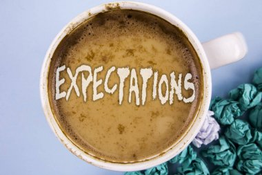 Conceptual hand writing showing Expectations. Business photo showcasing Huge sales in equity market assumptions by an expert analyst written on Coffee in Cup on plain background Paper Balls.