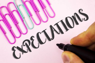 Word writing text Expectations. Business concept for Huge sales in equity market assumptions by an expert analyst written by Man holding Marker on Plain Pink background Paper Clips next to it.