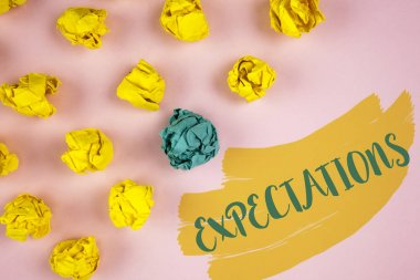 Handwriting text writing Expectations. Concept meaning Huge sales in equity market assumptions by an expert analyst written on Painted background Crumpled Paper Balls next to it.