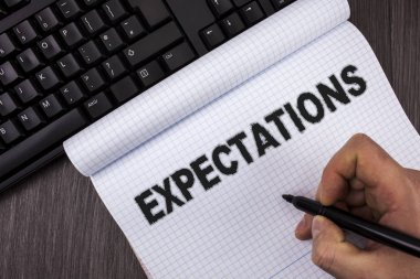 Conceptual hand writing showing Expectations. Business photo text Huge sales in equity market assumptions by an expert analyst written by Marker in Hand on Notebook on wooden background Keyboard
