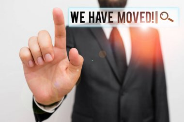 Text sign showing We Have Moved. Conceptual photo To go from one residence or location to another Relocate Male human with beard wear formal working suit clothes raising one hand up.