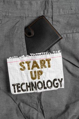 Writing note showing Start Up Technology. Business photo showcasing Young Technical Company initially Funded or Financed Small wallet inside trouser front pocket near notation paper.