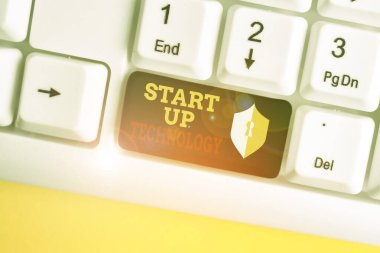 Text sign showing Start Up Technology. Conceptual photo Young Technical Company initially Funded or Financed White pc keyboard with empty note paper above white background key copy space.