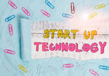 Writing note showing Start Up Technology. Business photo showcasing Young Technical Company initially Funded or Financed Paper clip and torn cardboard on wood classic table backdrop.