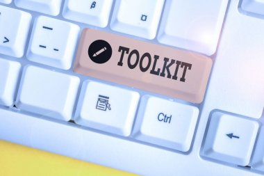 Text sign showing Toolkit. Conceptual photo set of tools kept in a bag or box and used for a particular purpose White pc keyboard with empty note paper above white background key copy space.