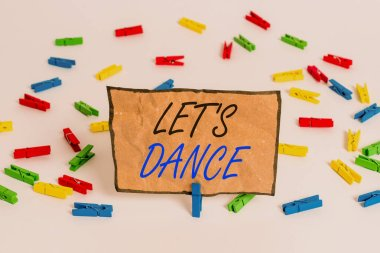 Handwriting text writing Let S Is Dance. Concept meaning move rhythmically to music following a set sequence of steps Colored clothespin papers empty reminder white floor background office.