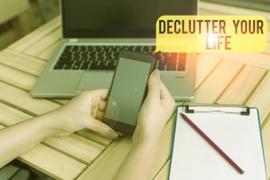 Handwriting text Declutter Your Life. Concept meaning To eliminate extraneous things or information in life woman laptop computer smartphone office supplies technological devices.