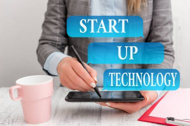 Writing note showing Start Up Technology. Business photo showcasing Young Technical Company initially Funded or Financed Business concept with mobile phone in the hand.