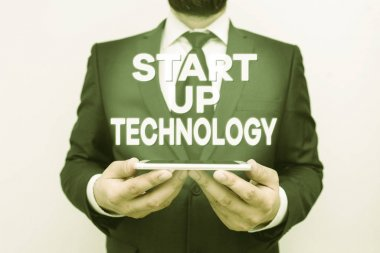 Text sign showing Start Up Technology. Conceptual photo Young Technical Company initially Funded or Financed Male human wear formal work suit hold smart hi tech smartphone use hands.